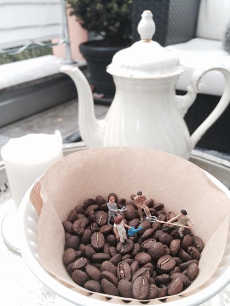 Miniaturfiguren arbeiten in Kaffeebohnen