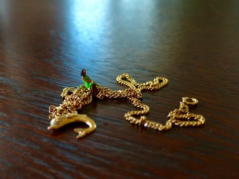 kleine Frau sitzt auf einer riesigen Goldkette mit DElphinanhänger und schaut bittend nach oben
