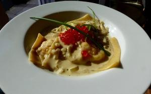 Lachsravioli auf Teller angerichtet mit heller Sauce und Kaviar