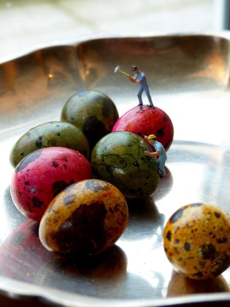 Miniatur-Arbeiter mit Vorschlaghammer auf buntem Wachtelei