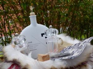 Ein Körbchen mit Olivenöl, Salz, Pfeffermühle und Servietten mit Besteck