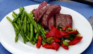 Flanksteak mit jungem grünem Spargel und Paprika-Gemüse auf dem Teller angerichtet