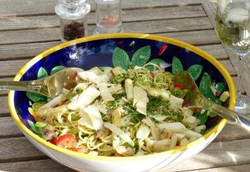 Spaghettisalat garniert mit Parmesan und Pinienkernen im Frühling