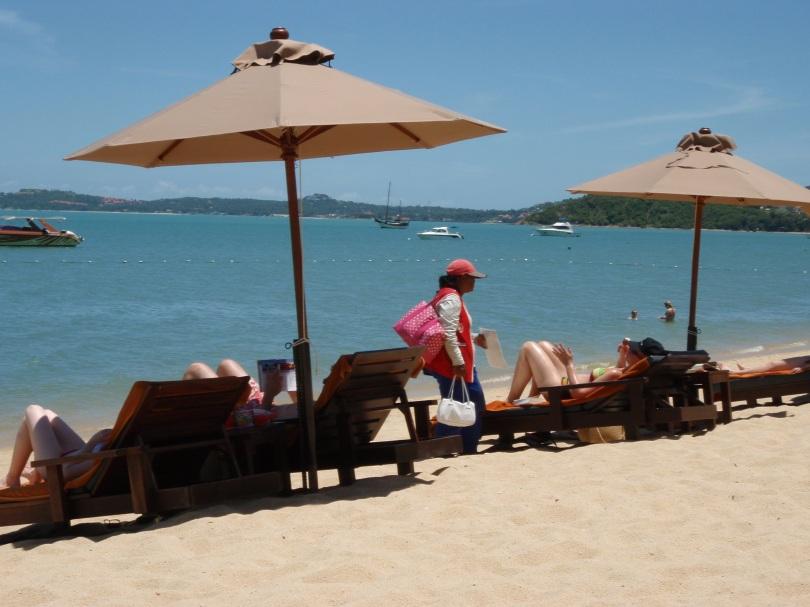 Strandverkäufer zwischen Liegestühlen auf Koh Samui
