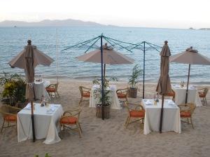 Tische und Schirme am Strand zum abendlichen Barbecue