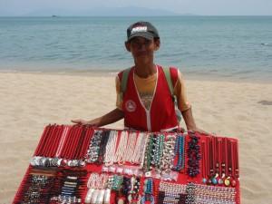 Straßenverkäufer mit Auswahl an bunten Ketten und Perlen