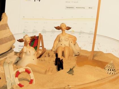sonnenbadende Figuren, im Hintergrund die Wettervorhersage