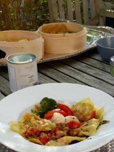 Ein asiatisches Gericht im Vordergrund, Bambus-Dampfkorb auf dem Tisch