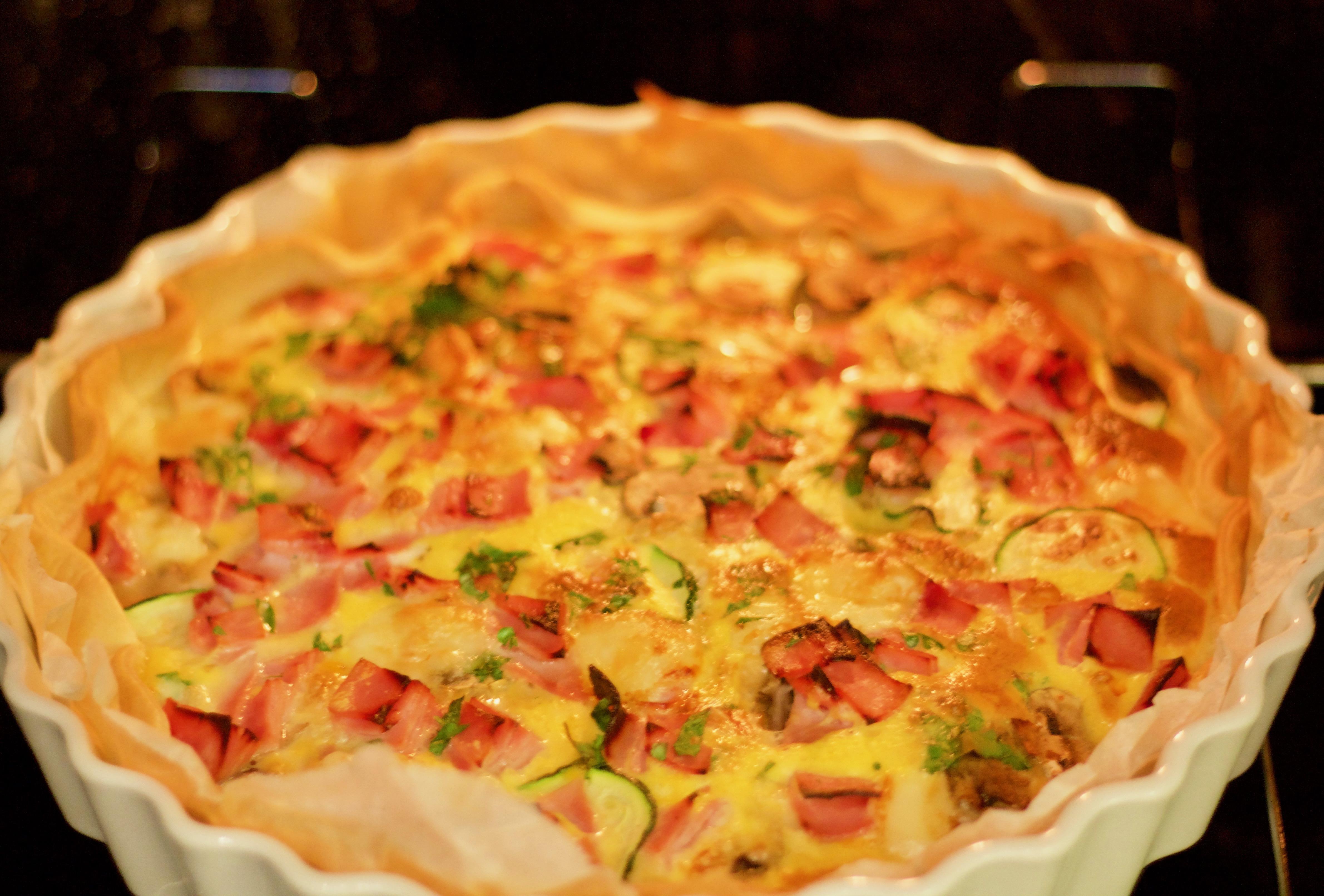 Fertige Quiche mit Schinken, Käse, Champignons und Zucchinischeiben im Backofen