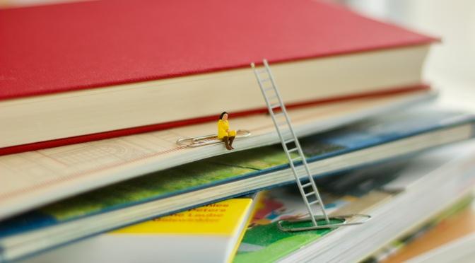 Miniaturfigur auf Bücherstapel Foto